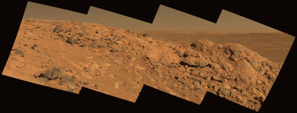 "This approximate true-color image taken by the Mars Exploration Rover Spirit shows a rock outcrop dubbed ""Longhorn,"" and behind it, the sweeping plains of Gusev Crater."