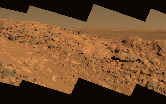 This approximate true-color image taken by the Mars Exploration Rover Spirit shows a rock outcrop dubbed 'Longhorn,' and behind it, the sweeping plains of Gusev Crater.