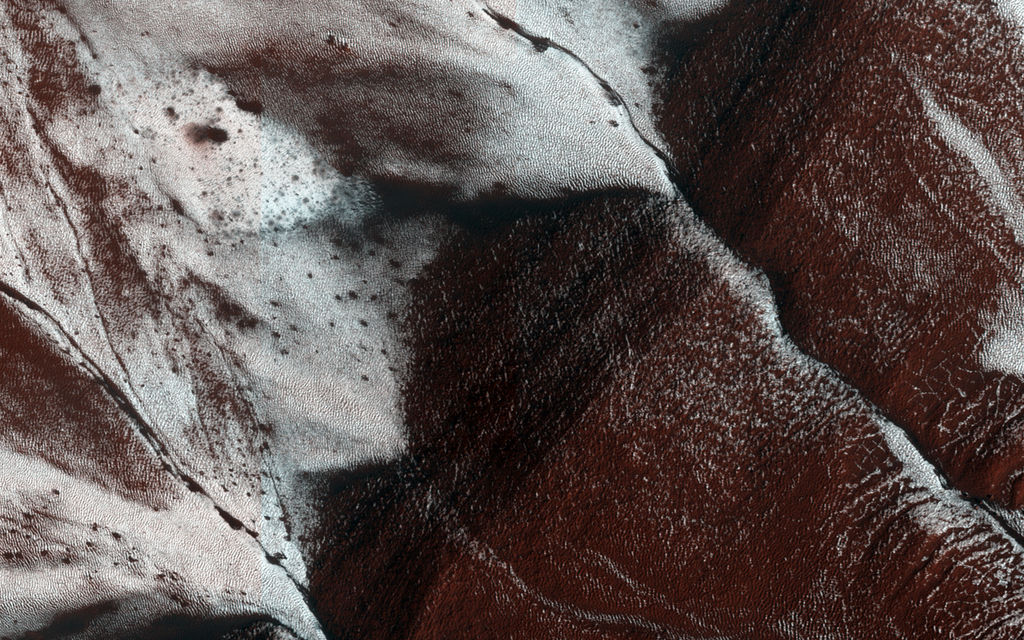 This HiRISE image shows gullies on a south-facing slope of a crater touched with late-Spring carbon dioxide frost.