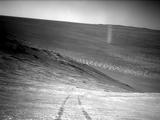 From its perch high on a ridge, NASA's Mars Exploration Rover Opportunity recorded this image of a Martian dust devil twisting through the valley below.