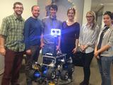 A group of six engineers stand in front of the ROV-E rover.