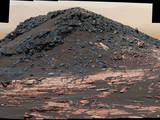 "This view from the Curiosity Mars rover's Mastcam shows a dark mound, called ""Ireson Hill,"" which rises about 16 feet above redder layered outcrop material on lower Mount Sharp, Mars, near a location where Curiosity examined a linear sand dune in February 2017."