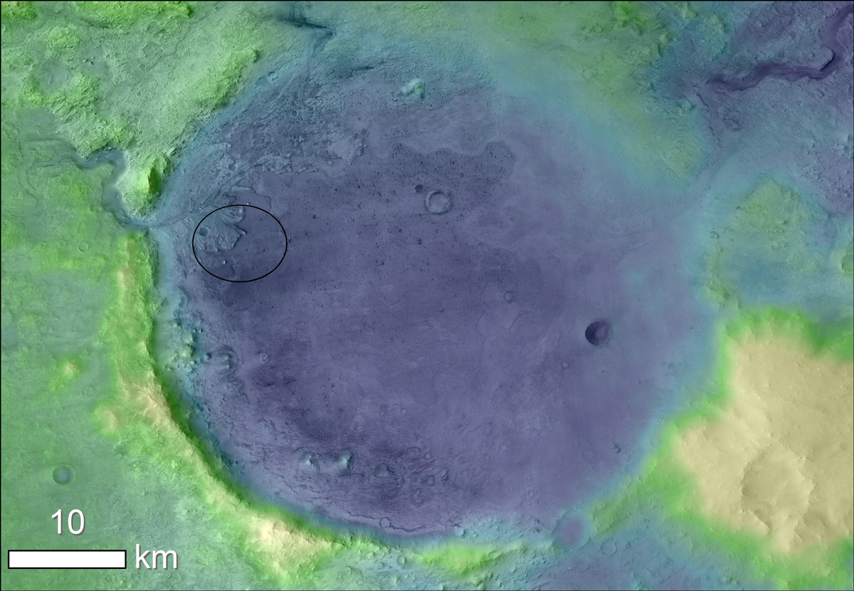 A false-color satellite image of Jezero Crater is green and yellow around the edges with a large blue circular crater in the middle.