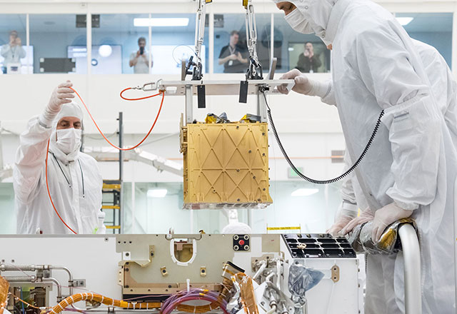 In a bright white cleanroom facility, technicians carefully lower a gold-colored cube – the MOXIE instrument – into the body of the Mars rover Perseverance.