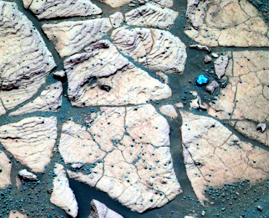 This striking, false-color image shows relatively flat, upward-facing, pinkish-white rocks with terraced surfaces insterspersed with cracks filled with turquoise-gray sand and pearl-shaped concretions.