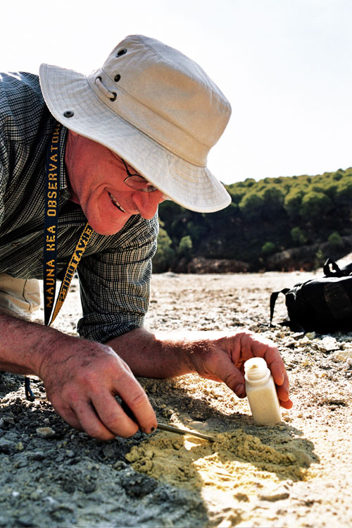 This photo, taken on the floodplain of the Rio Tinto in southwestern Spain, shows the head and shoulders of a man with a reddened, sun-weathered face wearing a white hat with a floppy brim hunched over a patch of yellow soil on the ground. In his right hand, he is using a pair of tweezeres to pick up soil sample and place them in a small, white, plastic vial that he is holding in his left hand. He is wearing a plaid shirt with the sleeves rolled up to his elbows and a black and yellow lanyard around his neck bearing the words, 'Mauna Kea Observatory.' A pair of black, wire-rimmed glasses protrudes slightly from beneah the brim of his hat. He is smiling. To his left is a black pack lying on the ground. Beyond him, in the distance, is a hill covered with shrubby green trees.