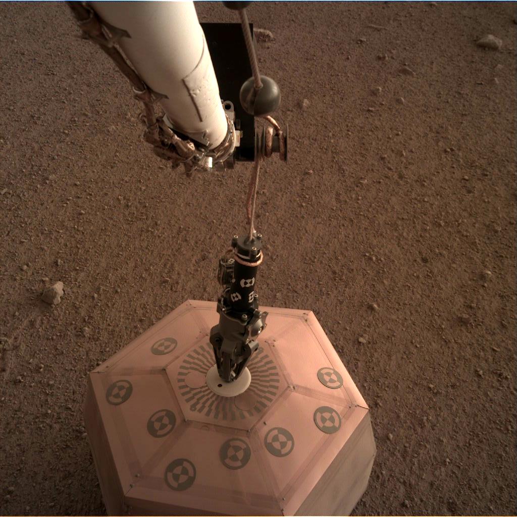Sonda InSight položila pomocí robotického ramene na povrch Marsu první vědecký přístroj - seismometr