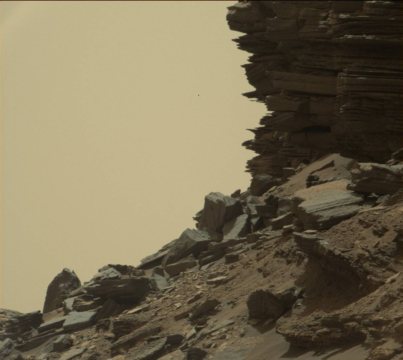 "This view from Curiosity shows a dramatic hillside outcrop with sandstone layers that scientists refer to as ""cross-bedding."""