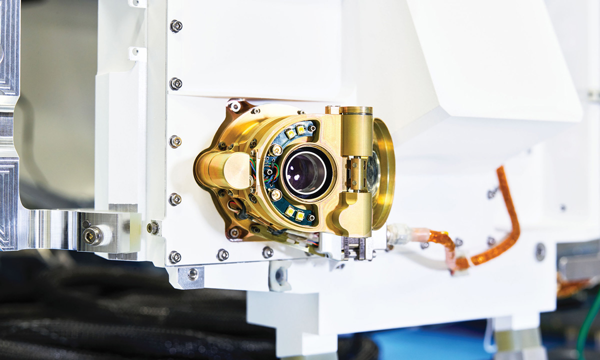 A small camera sits in gold-color housing on a white rover body.