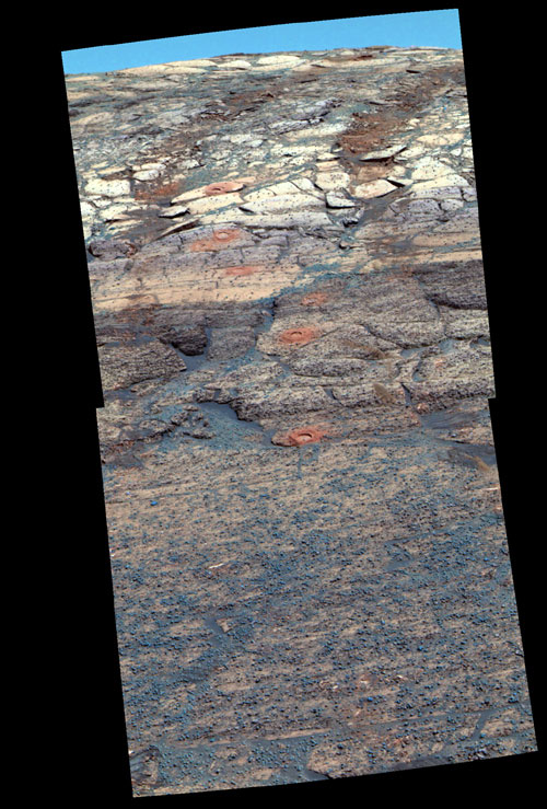This vertical panorama of an inside wall of Endurance Crater shows an eneven row of circular indentations extending from the middle of the panorama to the top edge of the crater. Each hole is ground into a different rock layer. The slope at the bottom nearest the camera is a pinkish surface dotted with blue-gray pearl-shaped rocks and sand. Above that, a horizontal layer of tan rock is overlain by successive layers of lavender, beige, and more lavender and beige rocks. In the upper third of the image mosaic, a pair of curving, vertical tracks can be seen where the rover's wheels have churned up two rows of coffee-colored soil.