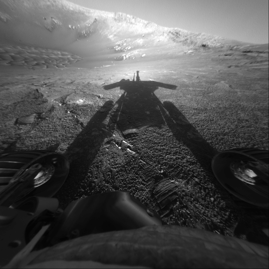 This image shows the opaque, elongated, late afternoon shadow of the rover extending upward from the bottom of the frame across a flat patch of bright, sandy ground in the direction of a precipitous drop on the rim of 'Endurance Crater.' The shadow consists of two long, black columns looking like a pair of thick planks tilted toward each other like the outer edges of the capital letter 'A.' They are the silhouette of the rover's wheels. Atop them is a blocky shadow with two lateral extensions reminiscent of arms held outward, topped by a vertical, narrow, pipe-like protuberance. These are silhouettes of the solar panels and the rover body topped by the rover's mast.