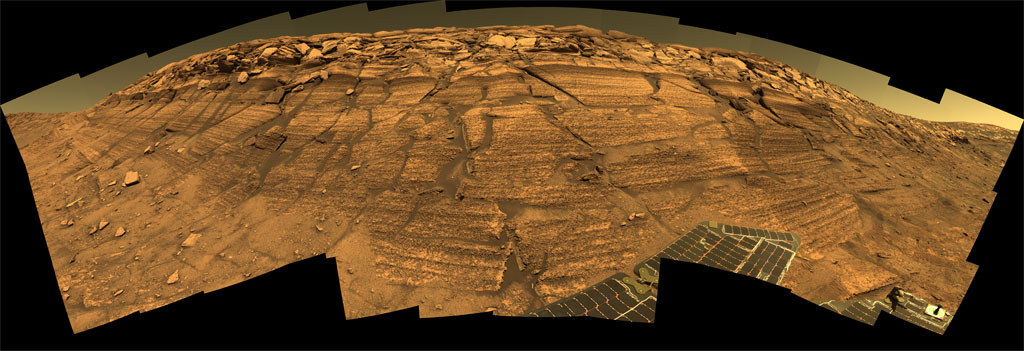 This horizontal color panorama of images shows an imposing stack of layers of rock topped by a cap of boulders. The entire outcrop is reddish-brown and is interspersed with cracks filled with grayish-brown sand. The leading edge of the rover's gray solar panels is visible at the bottom right in the foreground. In the left foreground, at the lower edge, are waves of sand lapping at the foot of the outcrop.