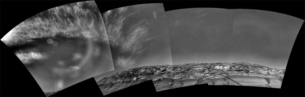 This panoramic mosaic of black-and-white images shows wispy, white clouds above the promontory of Burns Cliff.