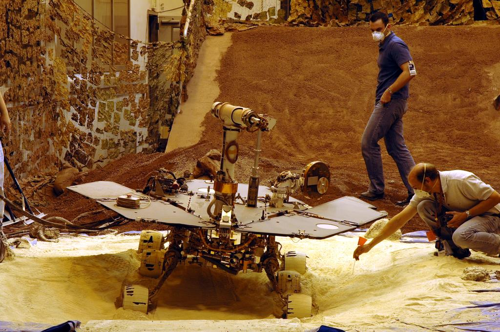 Engineers test moves on a model of the Opportunity rover in the In-Situ Instrument Laboratory at JPL