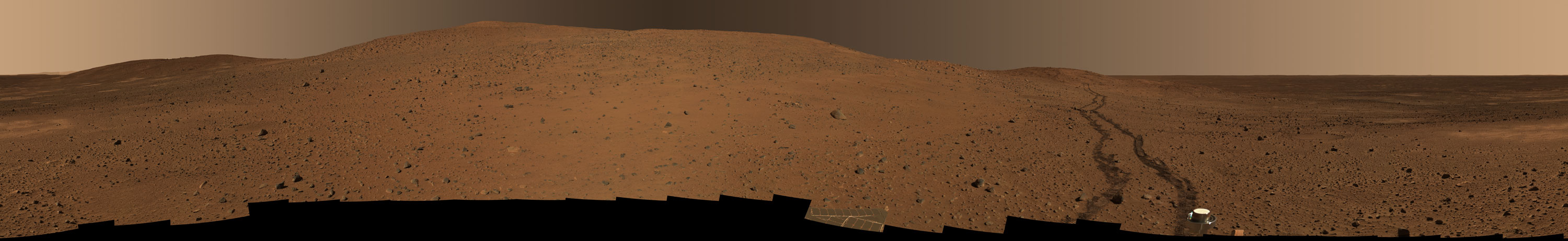 This sweeping color panorama shows a reddish-brown hill in the middle flanked by smaller hills on the right and left and the flat floor of Gusev Crater on the right. Two-thirds of the way across the image from the left, a pair of dark brown rover tracks meanders from the distant flank of the central hill toward the lower front edge of the scene.