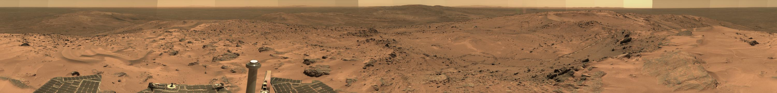 This approximate true-color panorama shows a broad, reddish-brown plateau covered with sand ripples and sprinkled with black rocks. On the lower left, the leading edge of the rover's solar panels and the silvery, metallic column of the UHF antenna are visible. In the distance are more hills, the flat floor of Gusev Crater, and a largely flat horizon bounded by a salmon-colored sky. Barely visible in th e middle horizon are the sloping peaks that make up part of the rim of Gusev Crater. Parts of the sky are darker and other parts are brighter as a result of changing amounts of dust in the atmosphere when the various images in the panoroma were taken.