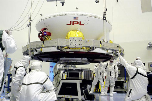 In a huge cleanroom at Kennedy Space Center, engineers wearing nearly all white 'bunny suits,' or protective gear, work on the Opportunity spacecraft which is inside its aeroshell.  Engineers are completely covered, except for their eyes, to keep contaminants off of the spacecraft.
