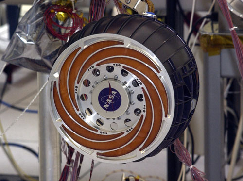This image features one of the Mars Exploration Rover wheels. They measure approximately 26 centimeters (a little over ten inches) and are aluminum with a black anodized coating on the paddlewheel-like driving surface. This up-close photo shows the spiral flectures which act as shock absorbers. The flectures radiate from the center of the wheel and resemble the rims on Earth-bound cars. Orange Solimide fills the flectures, preventing rocks and debris from interfering with the driving and steering actuators.