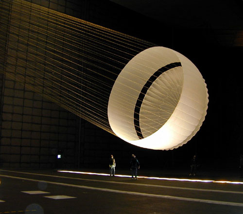 Inside of the world's largest wind tunnel at NASA's Ames Research center, the Mars Exploration Rover parachute is fully deployed. The parachute went through many design iterations to perfect it for use by the rovers in January, 2004. The rover chute is a narrow, conical design topped by minimal white fabric bands.