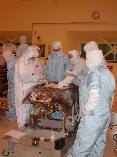 About a dozen engineers and technicians in cleanroom smocks labor over the rover's gold warm electronics box (WEB) in JPL's large cleanroom in the spacecraft assembly facility. The WEB box that is located at the center of both rovers houses the 'brains,' or crucial electronics that control rover movement and instrument deployment.