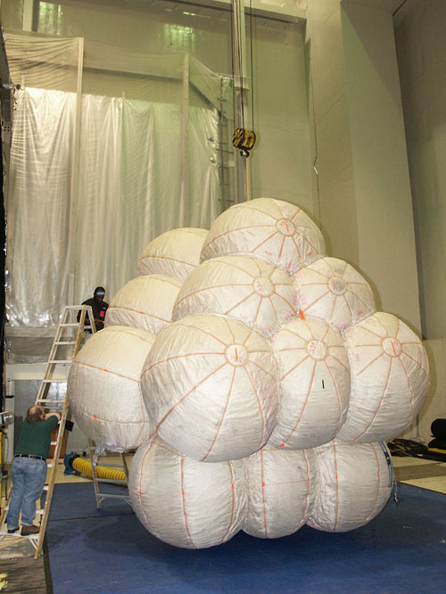 Looking like a giant cluster of white grapes or a bouquet of beach balls, a set of Mars Exploration Rover airbags sit, fully inflated, in a test facility. The image, demonstrating how massive they are, features two men on a very large ladder that only makes it about three-quarters of the way up the airbags 18-foot (5.5-meter) height.