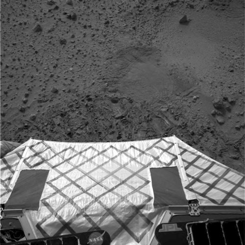 This image shows the view from the Mars Exploration Rover Spirit of the batwing with the surface of Mars in the background.