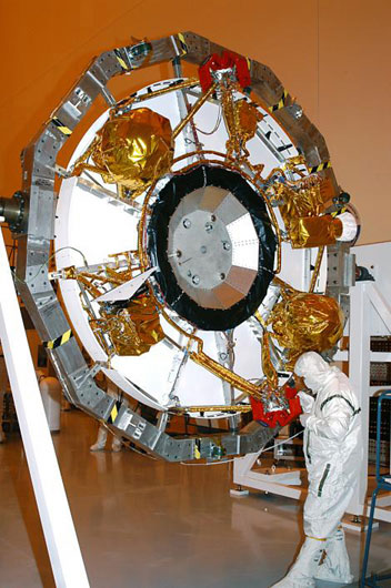 A technician is working on Opportunity's cruise stage, the part of the spacecraft responsible for guiding and fueling the trip to Mars. A large white and silver ring features propellant tanks covered in shiny gold Kapton material that serves as an insulator. In the center of the larger ring sits a smaller, black ring, inside of which are housed the antennas used to communicate through the long journey to Mars.