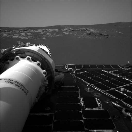 To the extreme left of the image, the rover's 'neck,' or panoramic camera mast assembly is stowed on top of the solar panels. In front of the rover lies the captivating outcrop in 'Eagle Crater' that became the first intense target of interest during the mission.