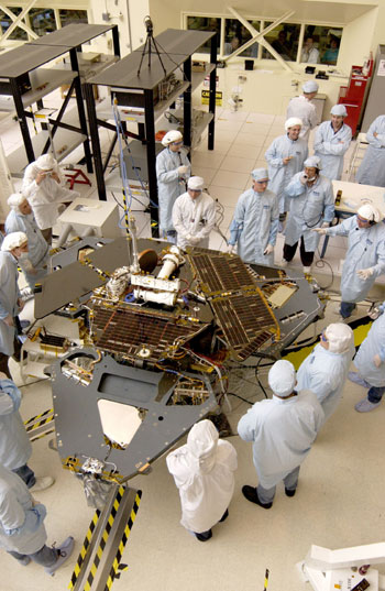 Over a dozen engineers and technicians in white and blue cleanroom smocks and bonnets look over the Spirit rover in JPL's large spacecraft assembly room. The solar panels are down so the team can delicately place solar cells on the rover 'wings.' These cells absorb sunlight, which powers the rover.