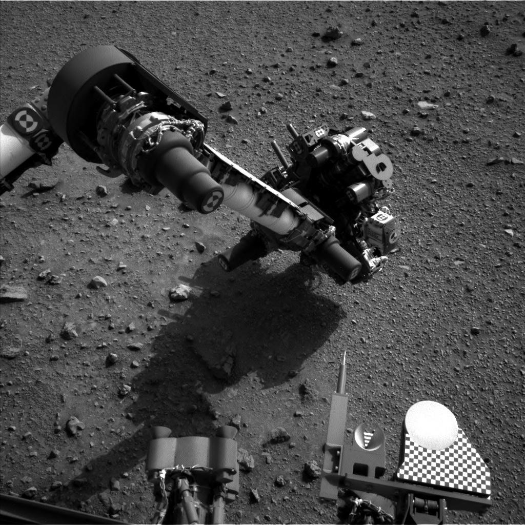 Curiosity's arm above the pile of dumped Telegraph Peak powder