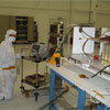 This picture is inside a large 'clean room,' where ATLO (Assembly, Testing, and Launch Operations) is taking place for the Mars Science Laboratory mission. In the foreground on the right are electronic components and to the left is a man leaning over the components. He is dressed in all white protective clothing, including a face mask and gloves.