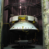 Here the Mars Science Laboratory spacecraft is suspended in a dark chamber, ready for an environmental test that simulates the extreme hold and cold temperatures of its journey to Mars. The spacecraft consists of a large ring (the cruise stage) on top with the aeroshell below (a clamshell-type structure that holds the rover and its descent stage).