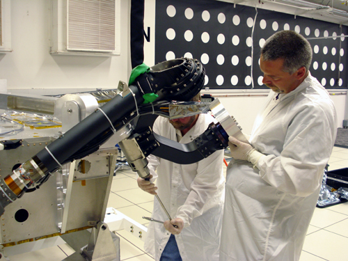In this image, two technicians from the Mars Science Laboratory team prepare the rover's mobility system for instrumentation tests. They are both wearing white coats and gloves as they each work on one of the rover's 'legs' in a white-tiled room.