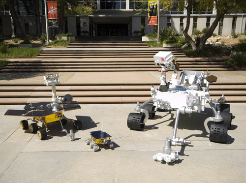 This image shows the front sides of three rovers viewed at an angle. On the right is the Mars Science Laboratory rover, which is the size of a small sport utility vehicle. Its 7-foot-long arm is extended in front of it, resting on the pavement. The camera 'eyes' at the top of its mast are turned downward at its smaller predecessors. In the middle, the tiny, wagon-size Sojourner rover has a deployable, alpha-particle X-ray spectrometer and single-color camera attached at its rear. On the left, the dune-buggy-size Mars Exploration Rover has its robotic arm extended in front of it, resting on the pavement. The panoramic camera 'eyes' at the top of its mast are turned upward, as if 'looking' at the bigger Mars Science Laboratory rover. All three rovers have six wheels, rocker-bogey suspension systems, rectangular bodies, solar panels, and antennas pointing upward from their spacecraft decks.