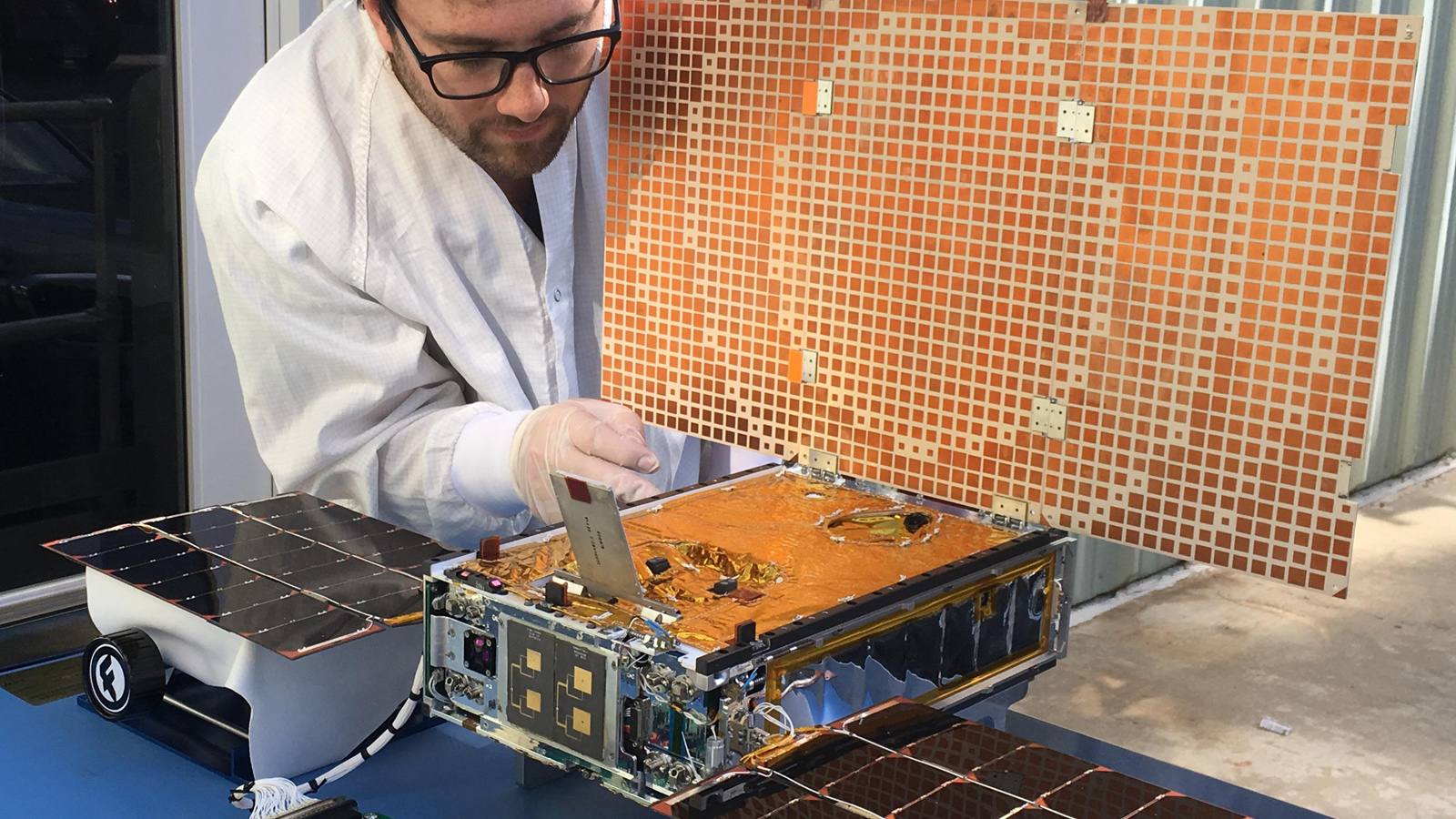 slide 4 - This is an image of a NASA engineer testing the solar arrays on one of the Mars Cube One, or MarCO, spacecraft.