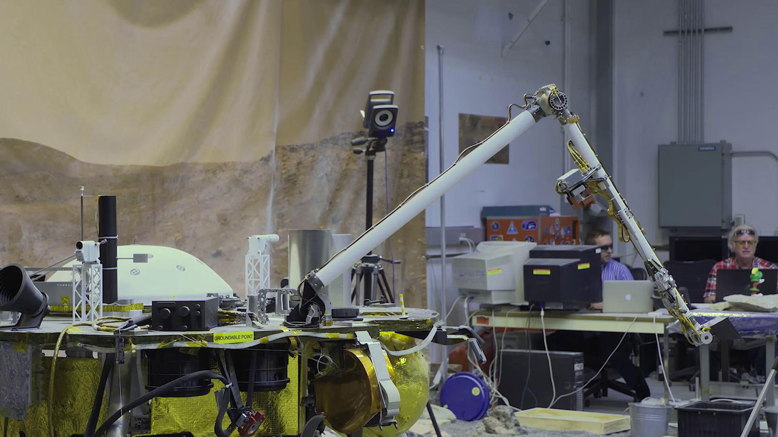 slide 1 - NASA's InSight mission tests an engineering version of the spacecraft's robotic arm in a Mars-like environment at NASA's Jet Propulsion Laboratory.