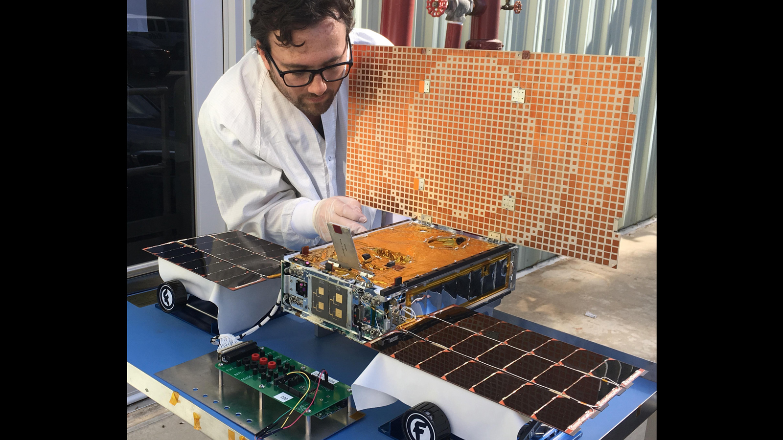 slide 5 - Engineer Joel Steinkraus tests the solar arrays on one of the Mars Cube One