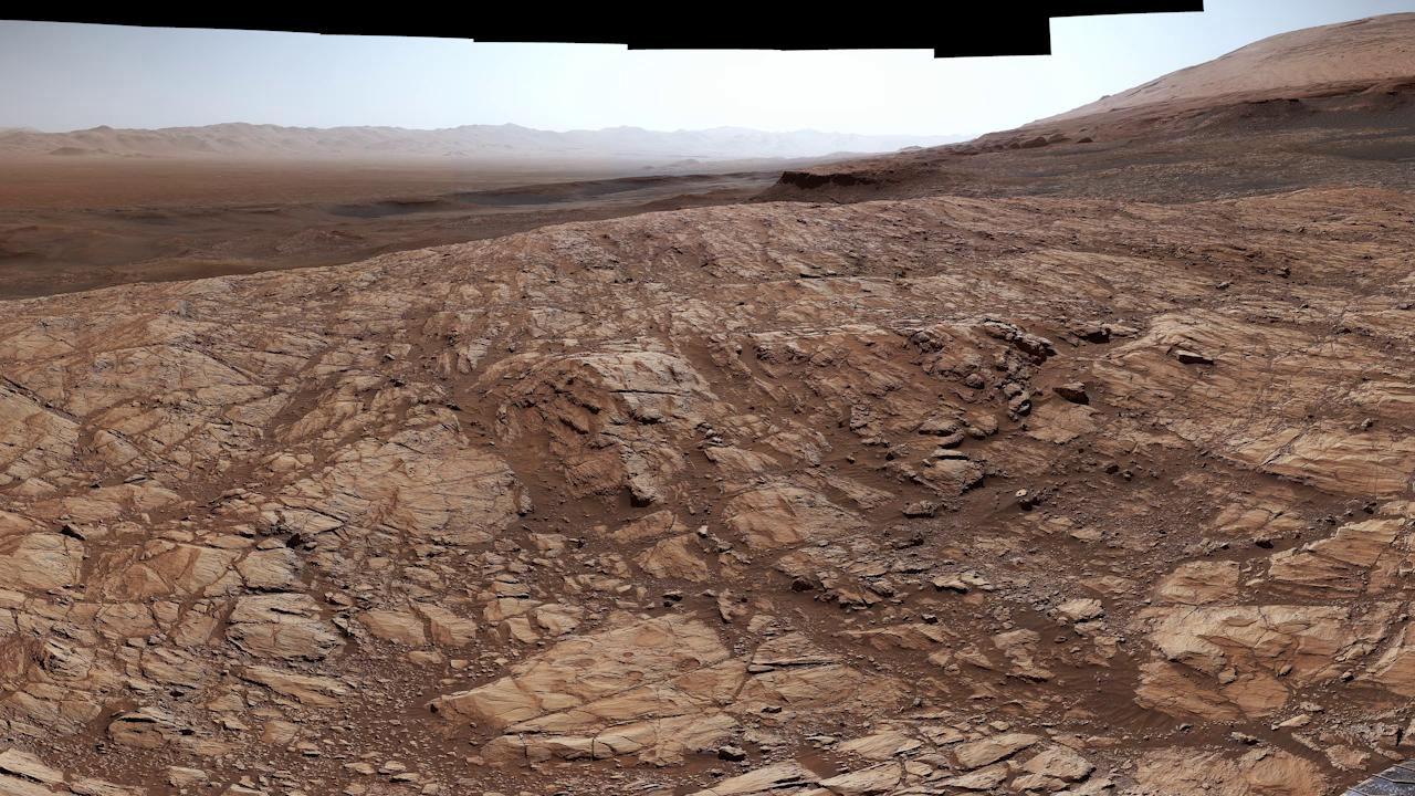 "slide 5 - NASA's Curiosity Mars rover captured this view from ""Greenheugh Pediment,"" the foreground is the pediment's sandstone cap. At center is the ""clay-bearing unit""; the floor of Gale Crater is in the distance."