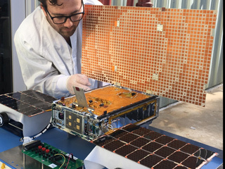 Engineer Joel Steinkraus uses sunlight to test the solar arrays on one of the Mars Cube One (MarCO) spacecraft.