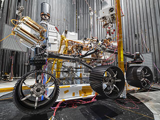 Ingenuity Mars Helicopter between left and center wheels of the Perseverance rover