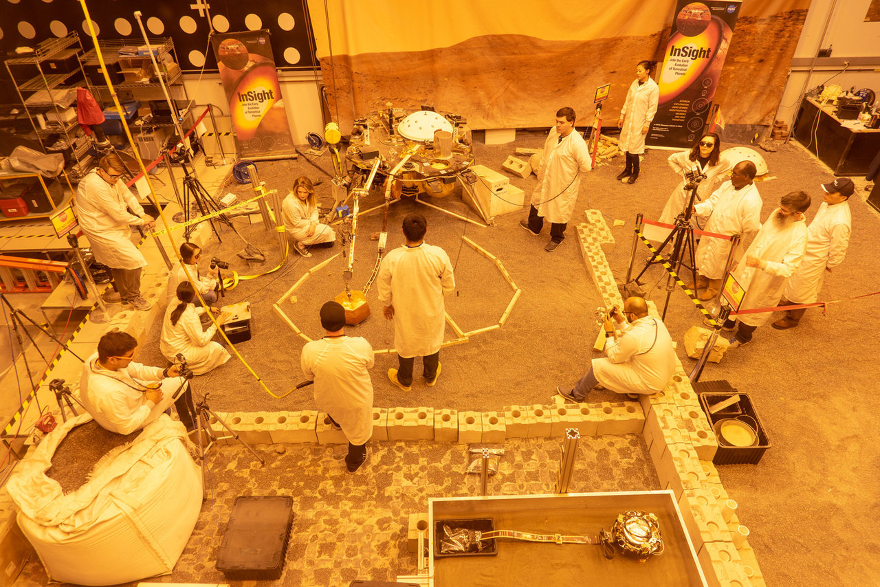 Engineers practice deploying InSight's instruments in a lab at NASA's Jet Propulsion Laboratory in Pasadena, California. Several of them are wearing sunglasses to block the bright yellow lights in the test space, which mimic sunlight as it appears on Mars.