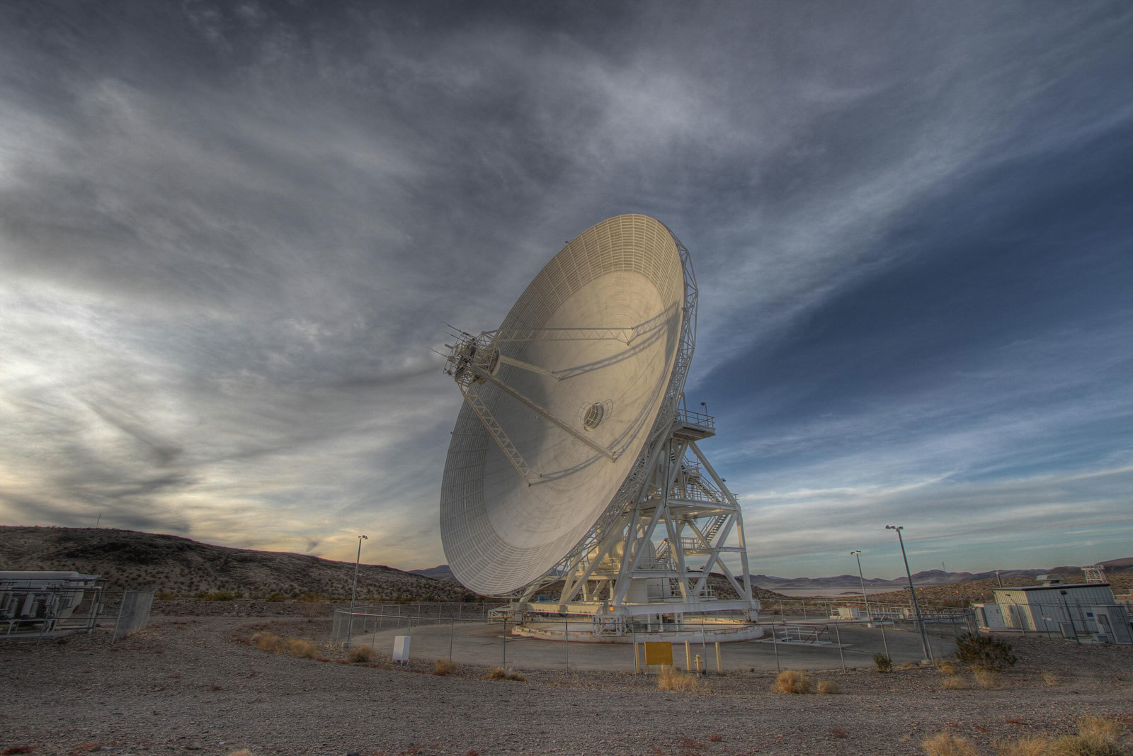 A Goldstone 111.5-foot (34-meter) beam-waveguide antenna tracks a spacecraft as it comes into view. The Goldstone Deep Space Communications Complex is located in the Mojave Desert in California.