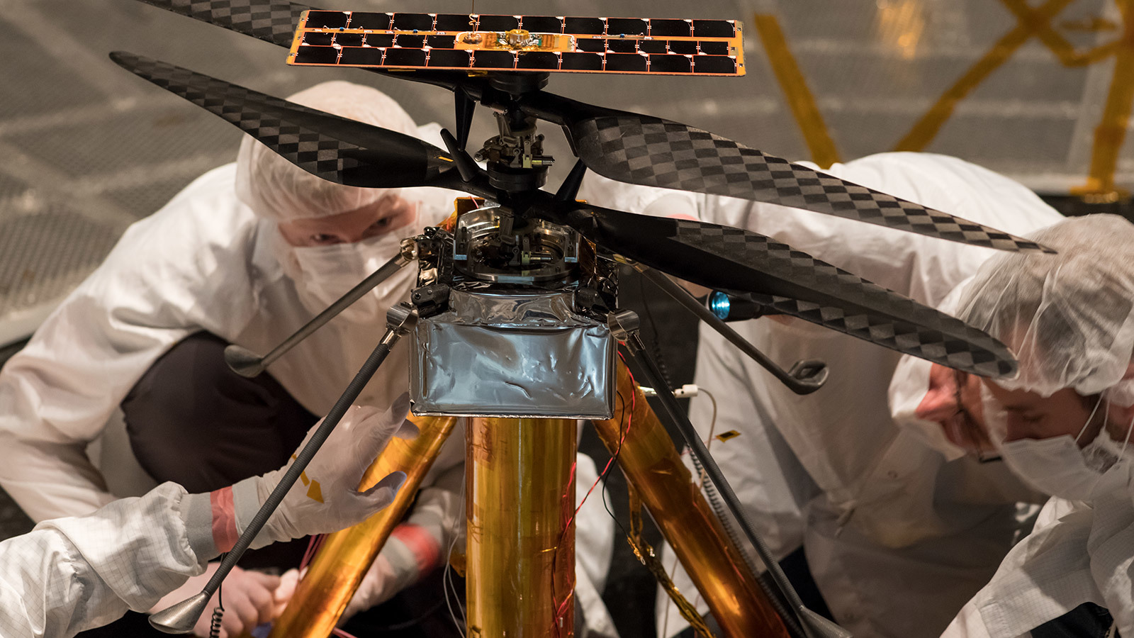 Members of the NASA Mars Helicopter team inspect the flight model.