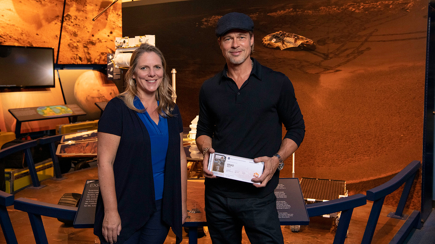 "The actor Brad Pitt (right) shows off his ""boarding pass"" for Mars with Jennifer Trosper (left), the Mars 2020 project systems engineer, at JPL on Sept. 6, 2019."