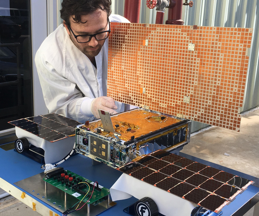 Engineer Joel Steinkraus tests the solar arrays on one of the Mars Cube One