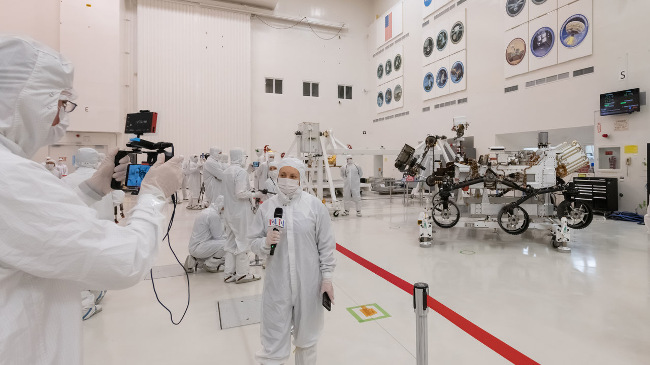 Members of the media interview the builders of the Mars 2020 mission inside JPL's clean room.