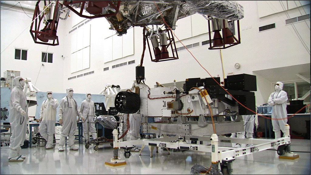 In this image, the car-size rover is in the middle of the picture with several team members surrounding it.  The team members are all dressed in special head-to-toe white suits, called 'bunny suits.'  One team member is holding on to a tether to guide the large insect-like descent stage down on top of the rover.  The descent stage looms high in this image.
