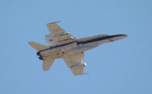 This image shows the underside of a grey F/A-18 jet with dark stripes flying against a blue sky from quite a distance away. Underneath the jet is a pod carrying sensors that measure the jet's temperature, pressure and vibration.
