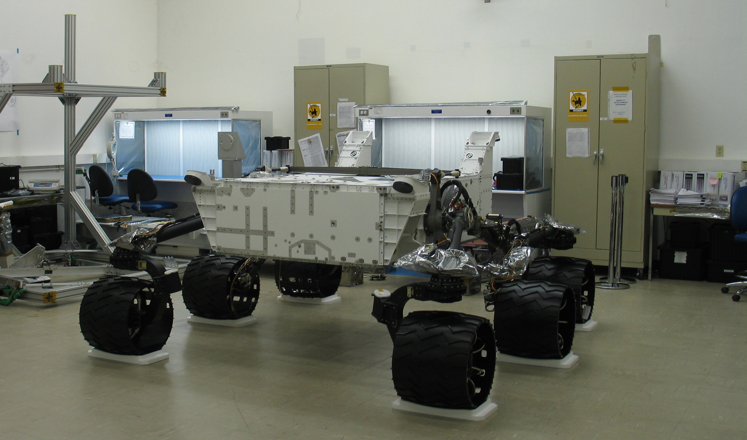 This image shows the body of the Mars Science Laboratory rover inside a clean room, supported by its six huge wheels and suspension system. Specially fitted platforms underneath the wheels hold the rover in place and prevent it from moving.