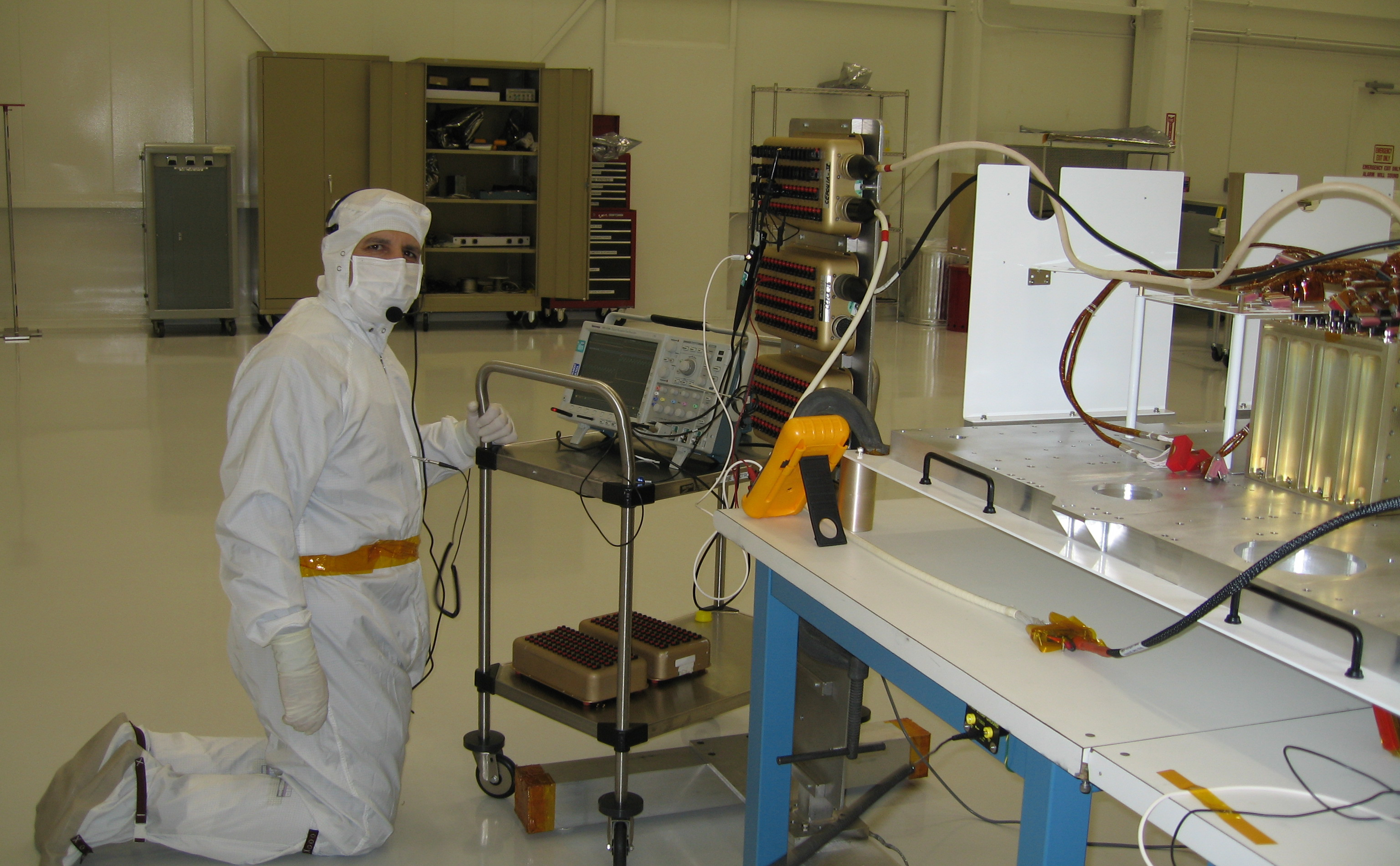 This image was taken inside a large 'clean room,' where ATLO (Assembly, Testing, and Launch Operations) is taking place for the Mars Science Laboratory mission. In the foreground on the right are electronic components and to the left is a man leaning over the components. He is dressed in all white protective clothing, including a face mask and gloves.